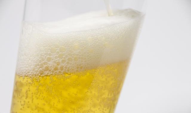 グラスにビールが注がれる様子